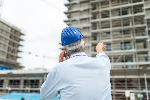 Architectmanager die op cellphone spreekt en zijn vinger richt op een bouwwerf
