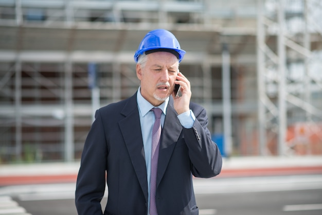 Architectmanager die op cellphone voor bouwwerf spreken
