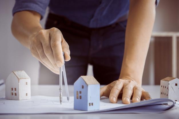 Architectmens die met kompassen en blauwdrukken werken voor architecturaal plan, ingenieur die een concept van het bouwproject schetsen.