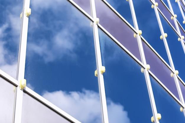 Architectonisch detail van de gevel met meerdere reflecties van andere gebouwen en de zon. buitenkant van modern gebouw. architectuur abstracte achtergrond