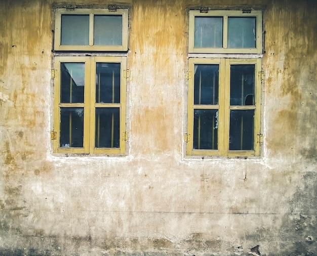 Architectonische details vintage raam met afbladderende verf in oranje. oude vintage raam van huis ouderwetse design klassieker op rustieke geschilderde betonnen muur achtergrond