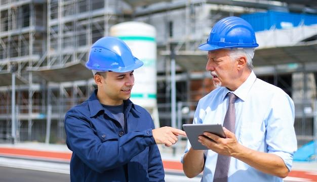 Architectontwikkelaars beoordelen bouwplannen op de bouwplaats met behulp van een tablet