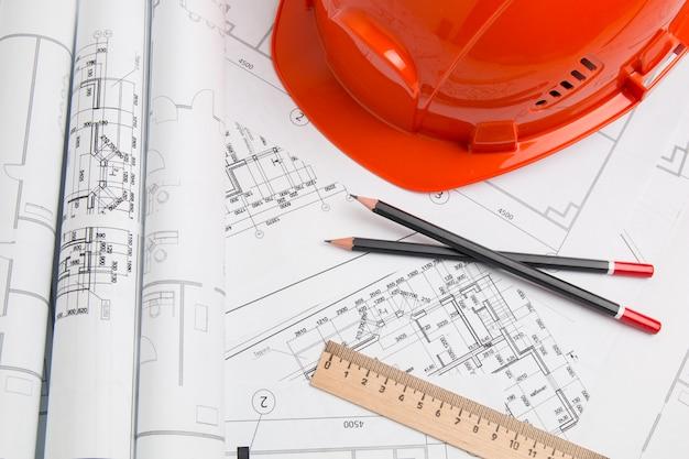Architecturaal plan. technische huistekeningen, helm, potloden en blauwdrukken.