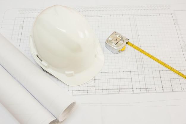 Architecturaal project, blauwdrukken, blauwdrukrollen, pen en meetlint op plannen.