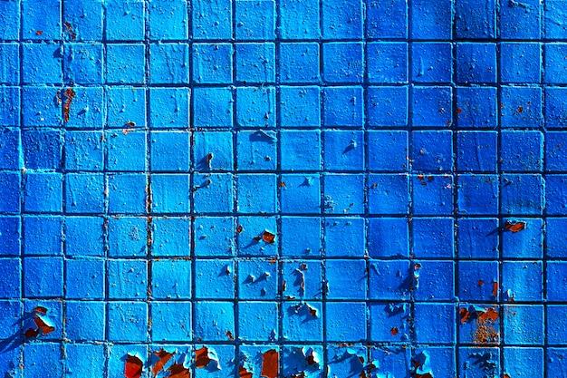 Architecturale achtergrond gemaakt van blauw geschilderde mozaïek muur met scheuren