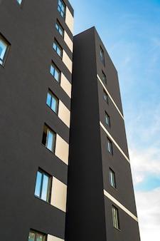 Architecturale details van modern flatgebouw tegenover blauwe hemel
