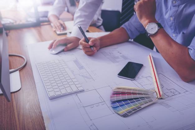 Architecturen bespreken gegevens werken schetsen op bouwkundig project op de bouwplaats.