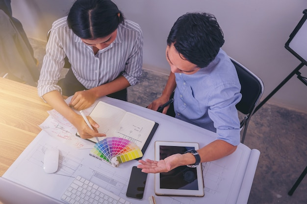 Architecturen die gegevens bespreken die het schetsen op architecturaal project en het kiezen van kleur bij bouwwerf bij bureau in bureau schikken
