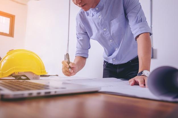 Architecturen werken schetsen op blauwdruk voor architecturaal project op bouwplaats aan de balie in kantoor