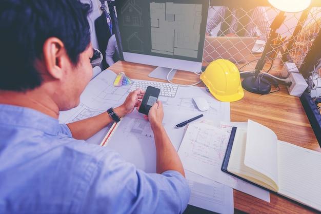 Architecturen werken schetsen op blauwdruk voor architecturaal project op de bouwplaats