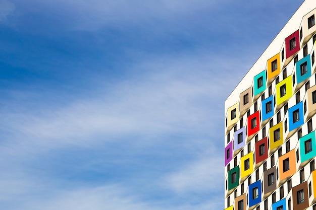 Architectuur op een achtergrond van blauwe lucht met wolken. moderne residentiële ontwikkeling. residentieel appartementengebouw met een felgekleurde gevel, balkons. architectuurontwerp.