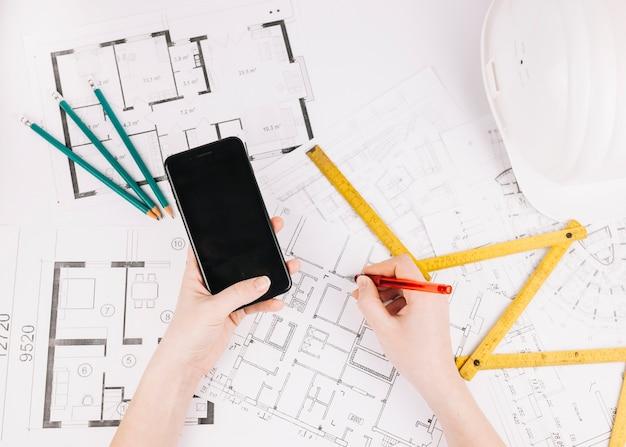 Architectuurconcept met de bouw van plan en smartphone