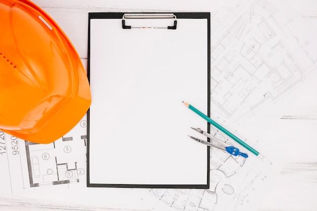 Architectuurconcept met klembord naast helm