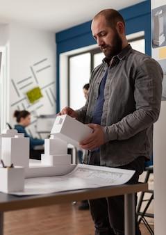 Architectuurdeskundige persoon die naar maquette kijkt