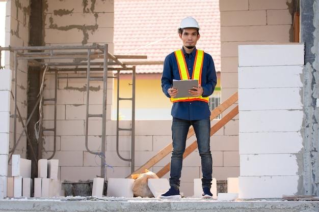 Architectuuringenieursarbeider die inspectiekwaliteitscontrole op bouwwerf doet