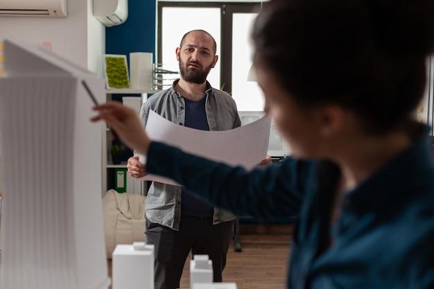 Architectuurwerkers controleren blauwdrukken met maquette