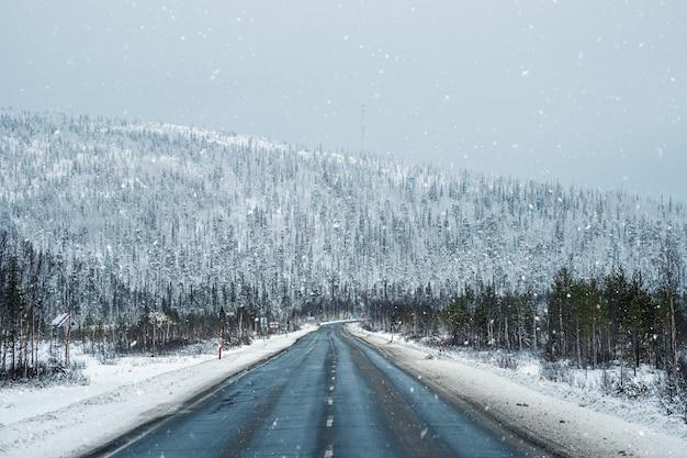 Arctische sneeuw rechte winterweg door de heuvels. sneeuw pas.