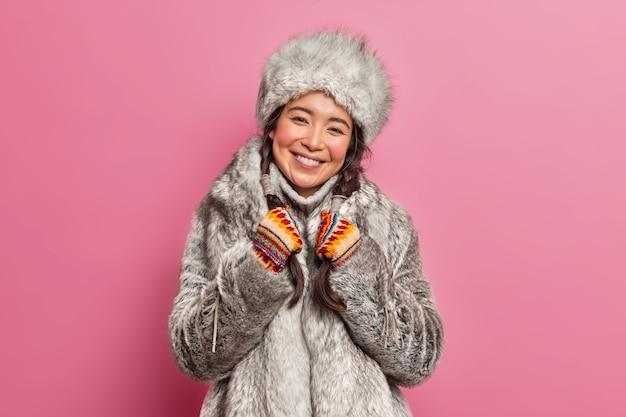 Arctische vrouw in winterkleren glimlacht in grote lijnen leeft in een koud klimaat glimlacht zachtjes houdt vlechtjes geïsoleerd over roze muur