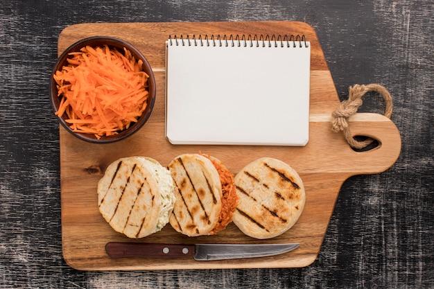 Arepas en notitieboekje op een houten bord