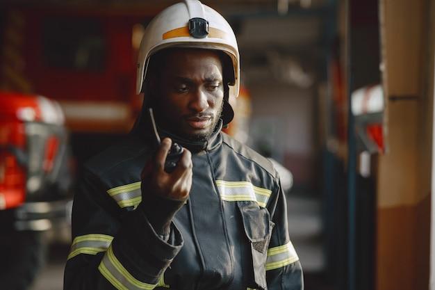 Arficaanse brandweerman in een uniform. man bereidt zich voor om te werken. kerel gebruikt radiozender.
