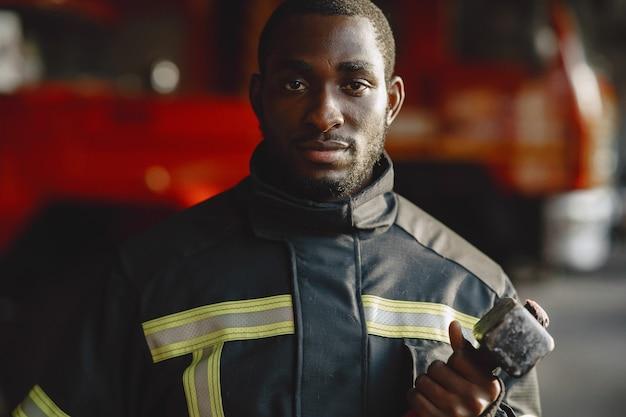 Arficaanse brandweerman in een uniform. man bereidt zich voor om te werken. kerel met hummer.