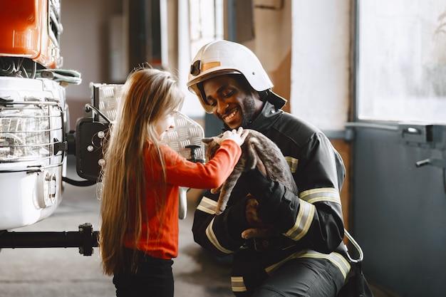 Arficaanse brandweerman in een uniform. man bereidt zich voor om te werken. man met kind.