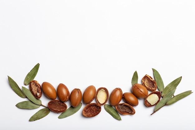 Argan zaden geïsoleerd op een witte achtergrond arganolie noten met plantaardige cosmetica en natuurlijke oliën terug...