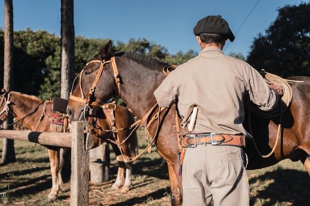 Argentijnse gaucho met paarden die werkkleding dragen, met gauchoslip en baret, traditionele argentijnse scène.