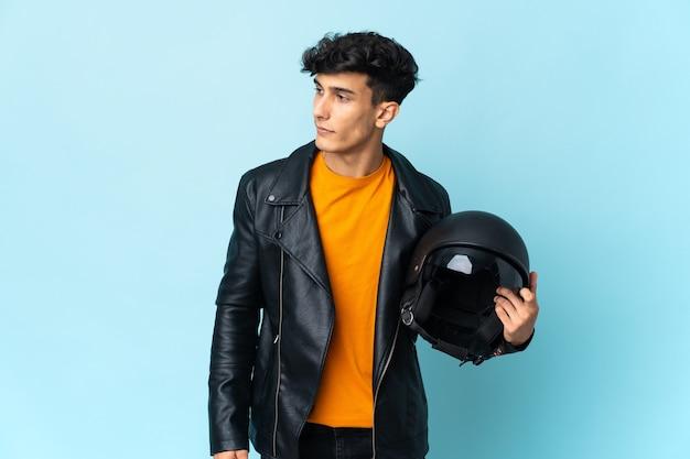 Argentijnse man met een motorhelm naar de zijkant kijkend
