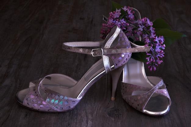 Argentijnse tango stiletto's en lila bloemen op donker hout