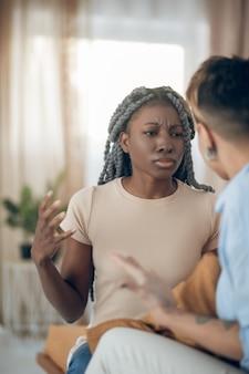 Argument. donkerhuidig meisje praat met haar vriendin en kijkt agressief