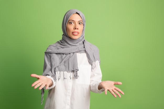 Argumenteren, argumenteren concept. arabische vrouw in hijab. portret dat van meisje, bij groene studioachtergrond stelt. jonge emotionele vrouw. de menselijke emoties, gezichtsuitdrukking concept. vooraanzicht.