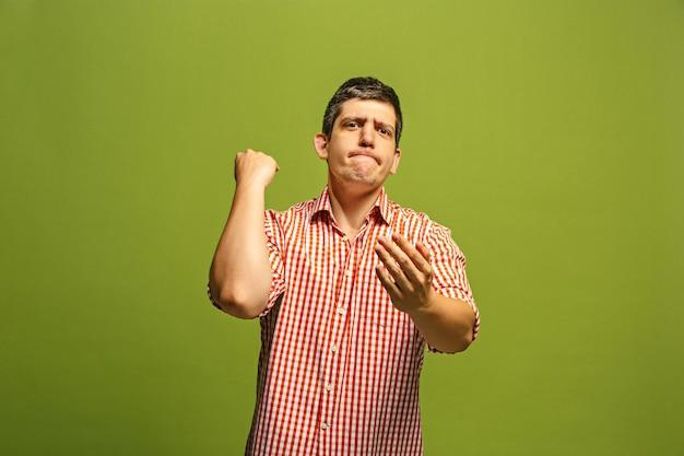 Argumenteren, argumenteren concept. grappige mannelijke halve lengte portret geïsoleerd op groene studio achtergrondgeluid. jonge emotionele verrast man camera kijken. vooraanzicht