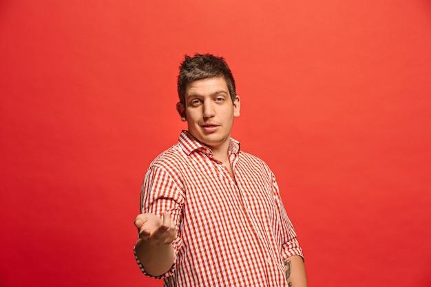 Argumenteren, argumenteren concept. grappige mannelijke halve lengte portret geïsoleerd op rode studio achtergrondgeluid. jonge emotionele verrast man camera kijken