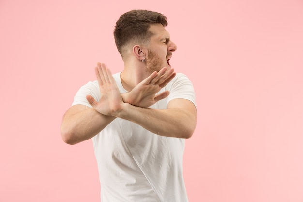 Argumenteren, argumenteren concept. mooie mannelijke halve lengte portret geïsoleerd op roze studio achtergrondgeluid. jonge emotionele verrast man camera kijken.