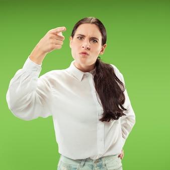 Argumenteren, argumenteren concept. mooie vrouwelijke halve lengte portret geïsoleerd op groene studio achtergrondgeluid. jonge emotionele verrast vrouw camera kijken. menselijke emoties, gezichtsuitdrukking concept