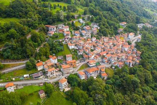 Arial uitzicht op berg italiaans dorp, garzeno. hoge hoekmening van huizen met rode daken onder bomen op de top van de berg in de zomer.