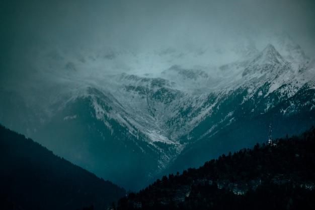 Ariel schot van beboste heuvels en besneeuwde berg in de verte