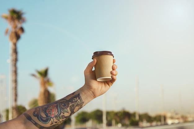 Arm en hand van een getatoeëerde man met een beige wegwerp koffiekopje van golfkarton tegen de helderblauwe lucht en palmbomen
