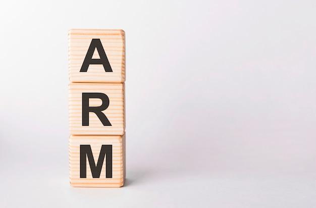 Arm letters van houten blokken in pijlervorm op witte achtergrond, kopieer ruimte