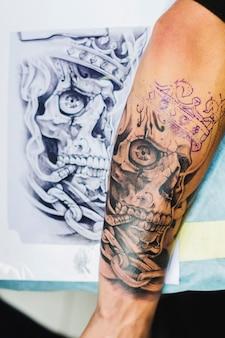 Arm met tatoeage dichtbij de schets