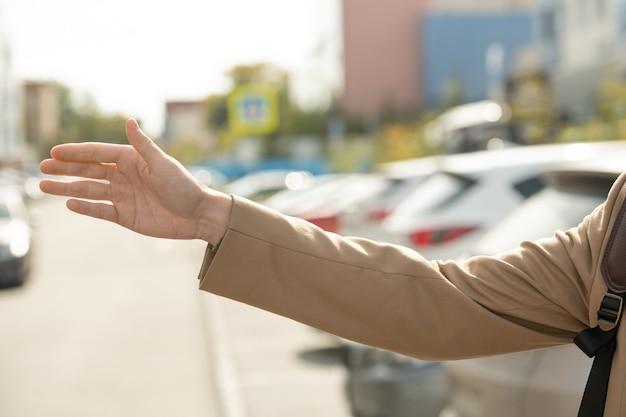 Arm van een jonge, drukke vrouw in een elegante beige trenchcoat die een taxi probeert te halen terwijl ze over de weg staat in een stedelijke omgeving