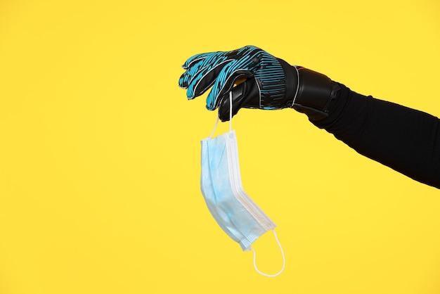Arm van een voetbaldoelman die een gezichtsmasker met zijn handschoen vasthoudt vanwege de coronaviruspandemie covid19 op een gele muur