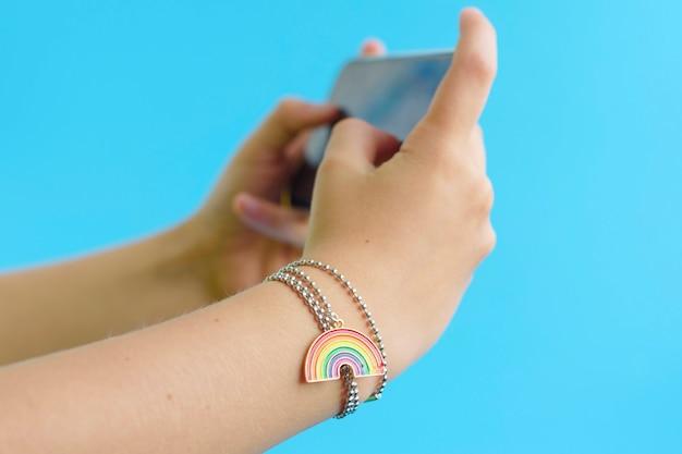 Armband met een hanger van regenboog op de arm, een concept van bescherming van minderheden
