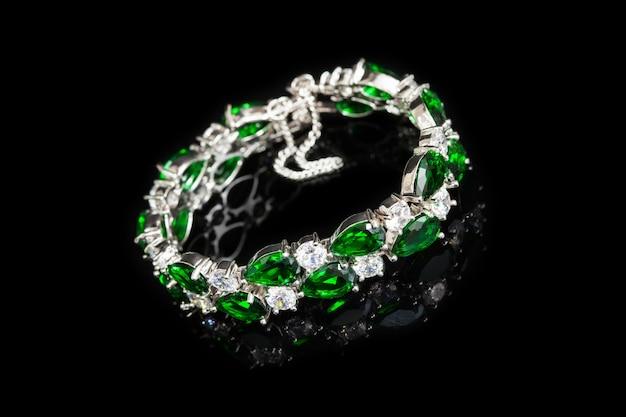 Armband met groene stenen die op zwarte, close-up worden geïsoleerd