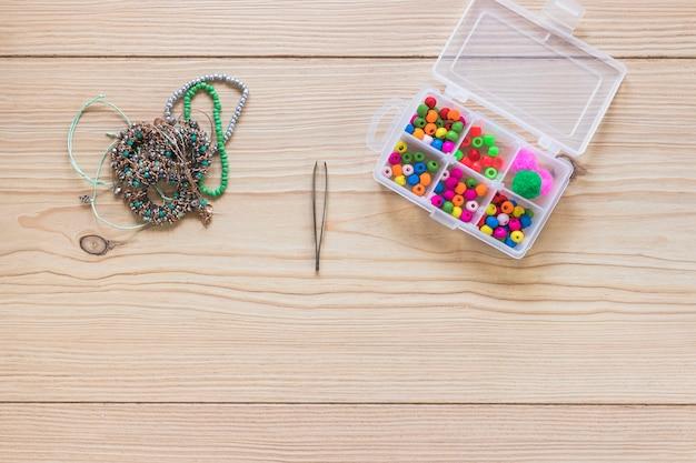 Armband; pincet en doos met kleurrijke kralen op tafel