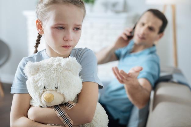 Arme blauwogige blonde meisje houdt haar speeltje vast en huilen terwijl haar vader aan de telefoon zit
