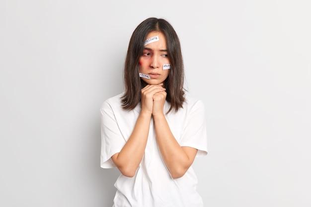 Arme hulpeloze vrouw kijkt bedachtzaam naar beneden heeft blauwe plekken op gezicht wordt slachtoffer van moordenaar lijdt aan ernstige sadistische martelingen heeft familieproblemen met echtgenoot gekleed in wit t-shirt. depressie wanhoop