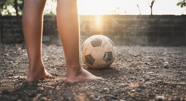 Arme jongen spelen van oude voetbal of voetbal op de grond met gloeiend zonlicht