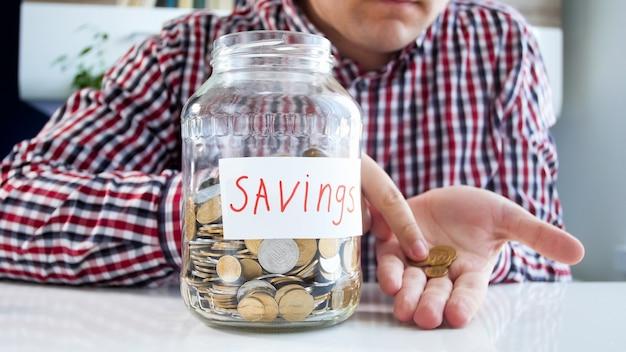 Arme man die enkele munten op zijn hand telt. concept van financiële crisis en baanverlies.